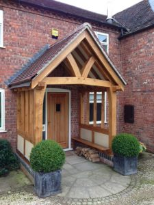 Oak framed porch with oak seat and side render panels