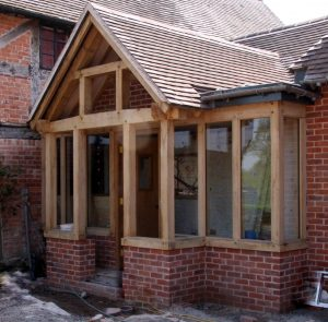 Large enclosed oak framed porch on a red brick house