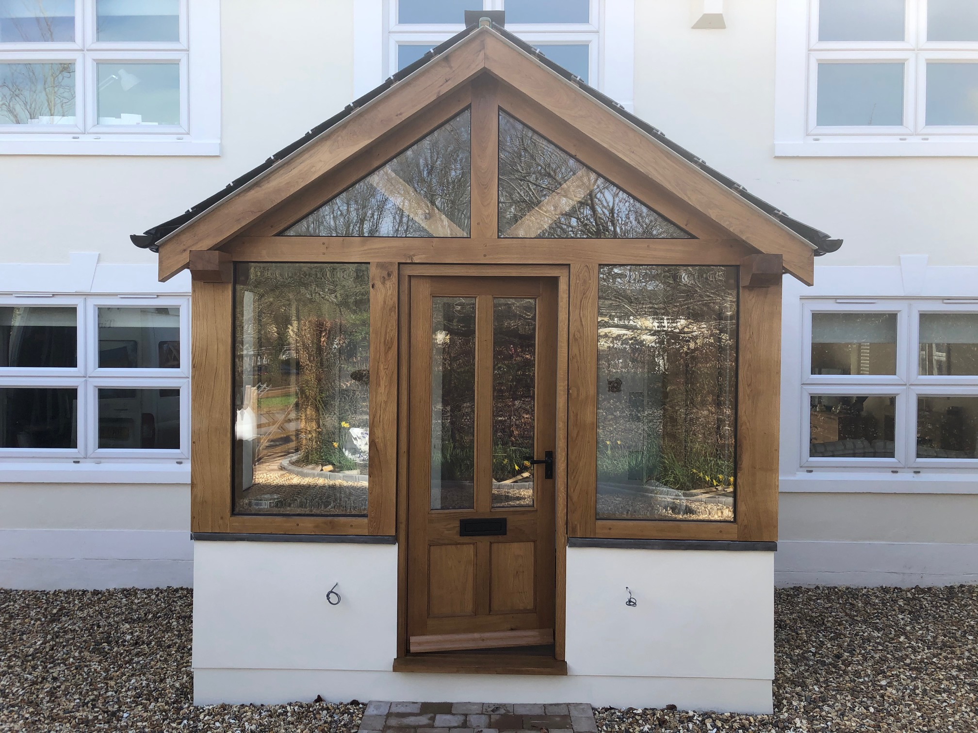 Enclosed oak porch with double glazed units and a slate roof