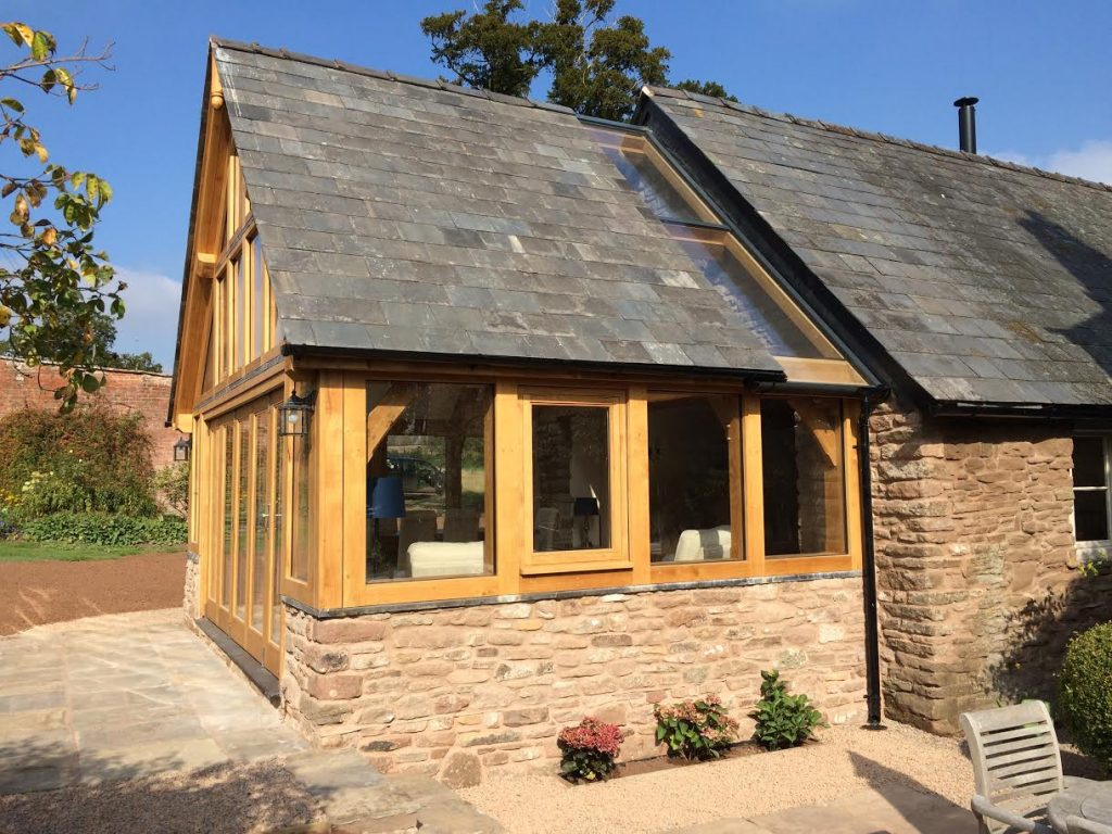 Oak framed sun room extension on stone wall