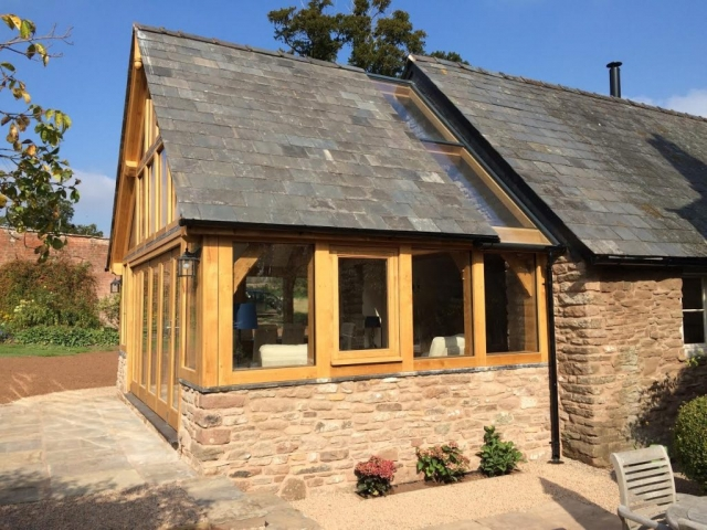 Glazed oak framed extension on stone wall