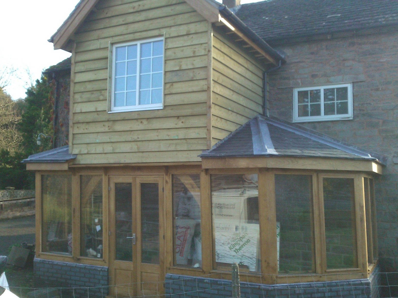 Glazed oak extension with two storey middle bay