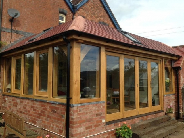 Oak framed garden room extension on a brick wall