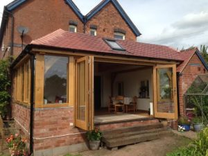 An oak framed conservatory with a set of oak bi folding doors opening up the room to the...