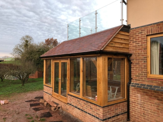 Oak framed garden room, side view with oak doors and balcony above.