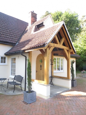 Oak Framed porch with curved braces on a rendered white wall