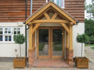 Oak porch with curved tie beam sat on a dwarf wall