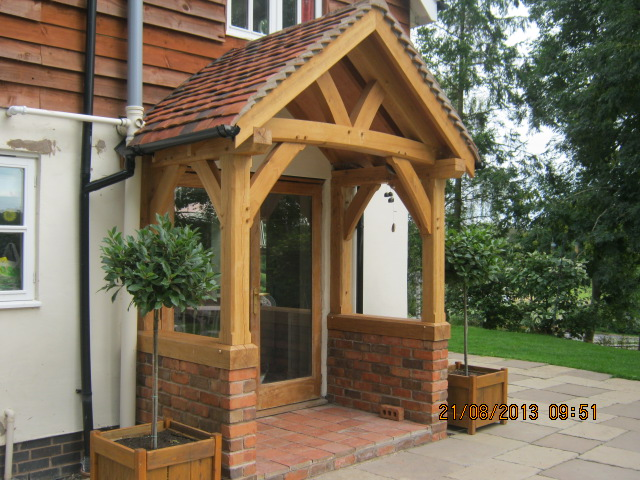Oak porch with curved tie and braces sat on a brick wall