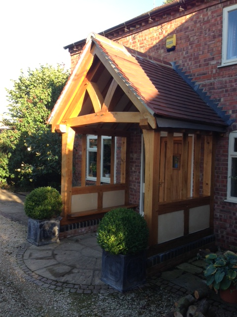 Oak porch with shaped tie beam and render panels