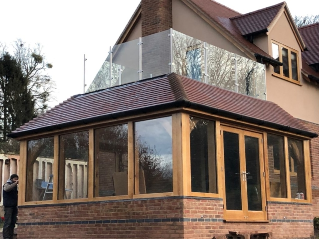 Oak framed garden room with balcony featuring glass balustrade