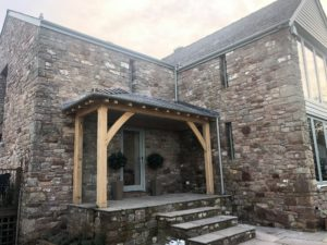 Oak lean too porch with a glazed side frame fitted onto a stone barn.