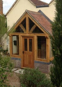 Enclosed oak porch with glazed gable and oak door.