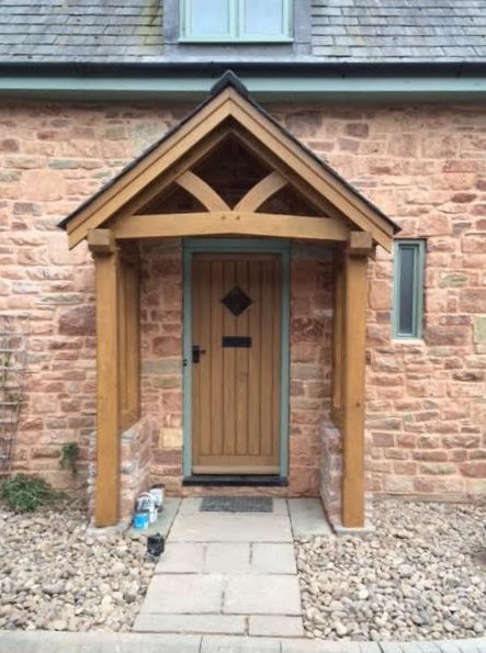 Oak porch with curved tie beam on a stone barn