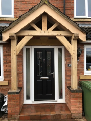 An oak porch fitted onto a modern red brick house.