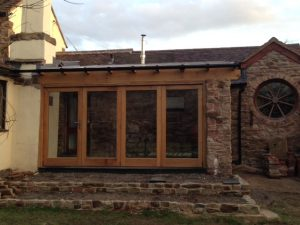 An oak framed garden room with a set of oak bi folds.