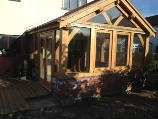 Oak frame conservatory sat on red brick wall