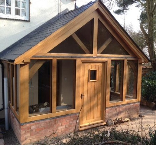 Large enclosed oak framed porch sat on red brick wall