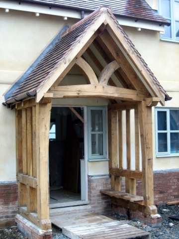 Oak framed porch with shaped tie beam and shaped front posts