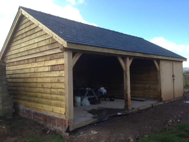 Triple bay oak framed garage with one bay enclosed