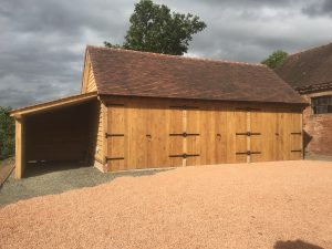 Triple bay oak framed garage with log store on the side