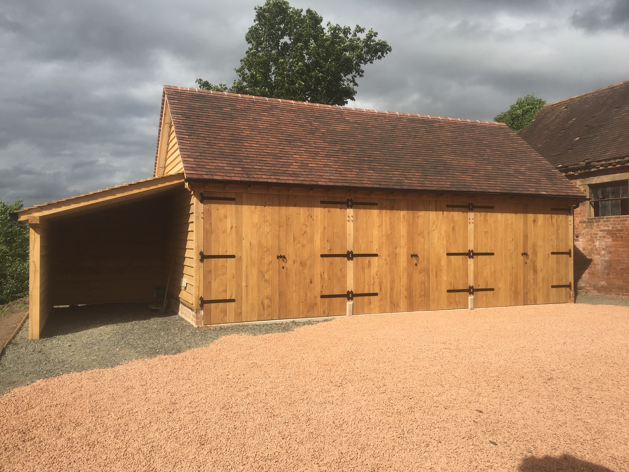 Triple bay oak framed garage enclosed with oak doors