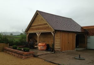 Two bay oak garage with log store