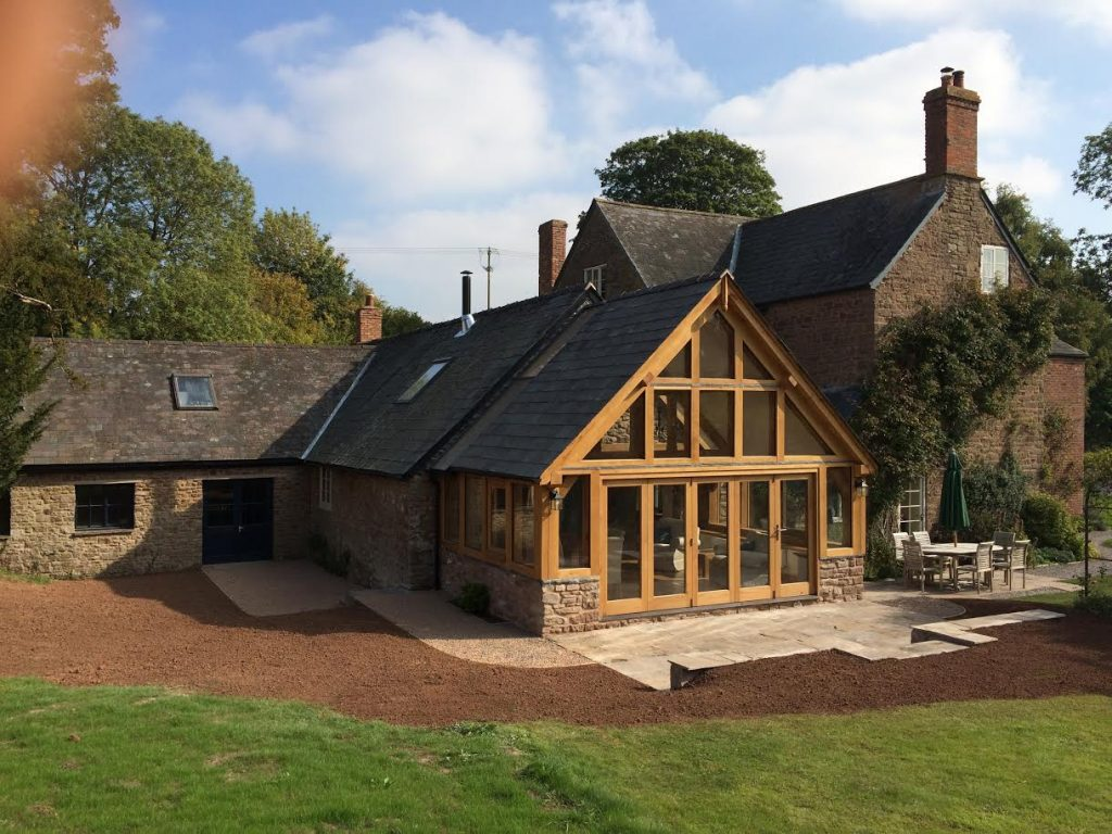 An oak framed sun room with a set of bi folding doors in the front.