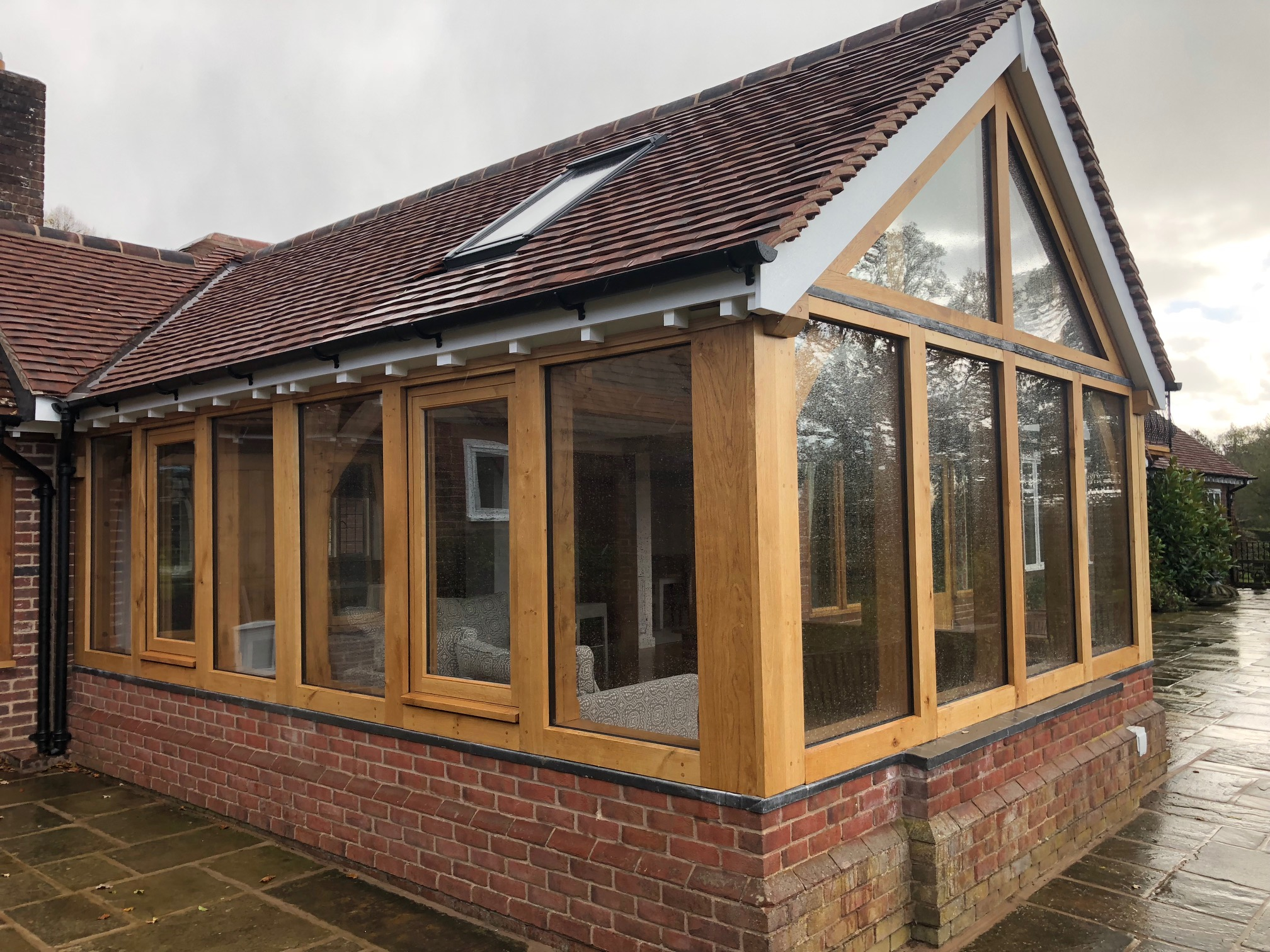 Oak framed garden room extension sat on a dwarf red brick wall