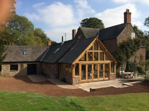 Oak and glass extension sat on a stone wall