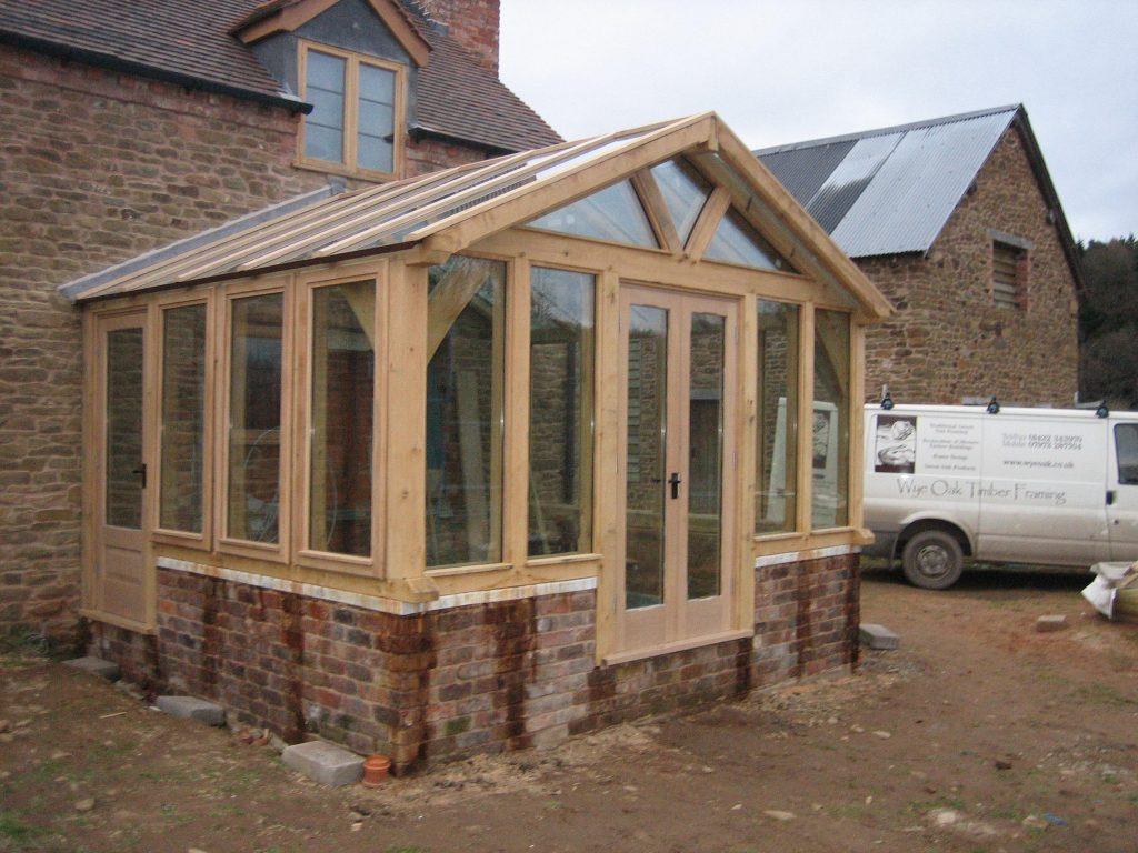 Oak framed extension fully glazed sat on red brick walls