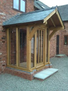 Enclosed oak porch with braced overhang