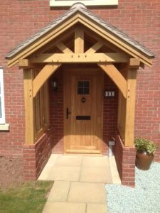 Oak Framed porch with curved braces sat on red brick wall