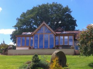 Large glazed oak framed extension with gable and lantern sections.