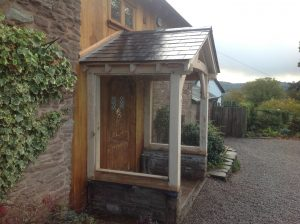 Side view of oak framed porch with slate roof