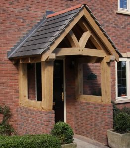 Oak porch with shaped tie beam sat on red brick walls
