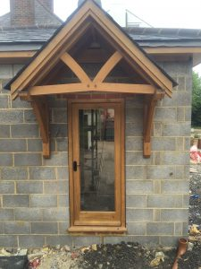 Oak canopy with a 45 degree pitch roof and an oak glazed door