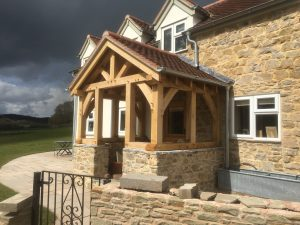Oak framed porch with curved braces in the corners sat on a stone dwarf wall