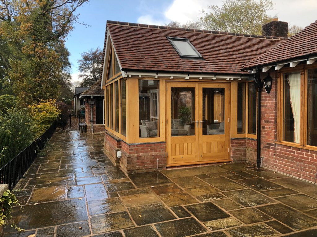 Oak framed sun room extension on a brick wall