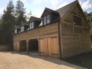 Two storey oak framed garage with two bays enclosed and two open bays